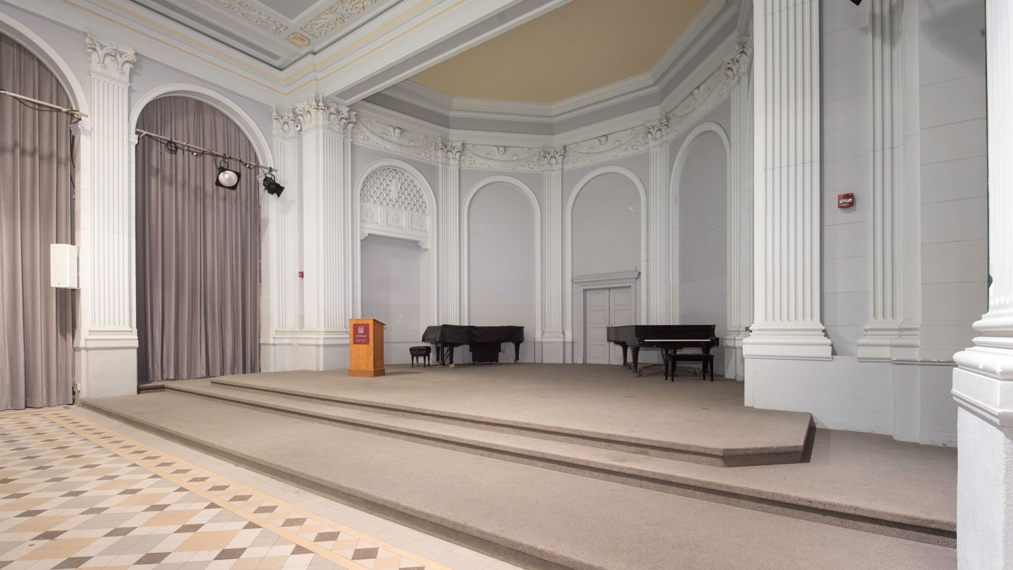 Carpeted stage with podium and two pianos